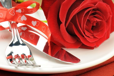 Closeup of red rose and cutlery on white plate photo