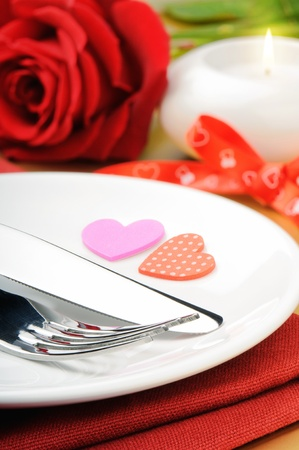 dinning table: Closeup of red rose and cutlery on white plate Stock Photo