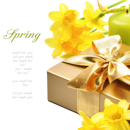Golden gift box with springtime narcissus over white photo