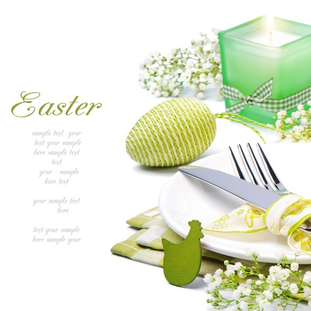 easter decorations: Easter table setting with candle and flowers over white Stock Photo