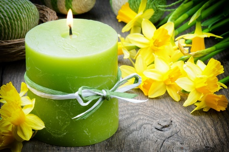 Spring setting with yellow narcissus and candle on the wooden table Stock Photo