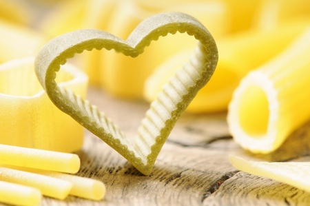Raw heart shaped pasta on wooden table