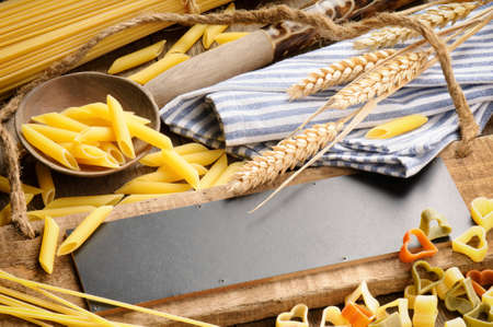 Rustic wooden board with pasta assortment and tablecloth photo