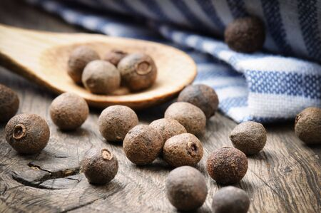 Allspice pepper on the rustic wooden table photo