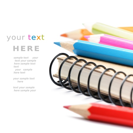secondary school: Colorful pencils and notebook isolated over white with copyspace Stock Photo
