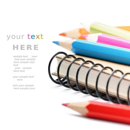 utiles escolares: L�pices de colores y un cuaderno aislado en blanco con copyspace
