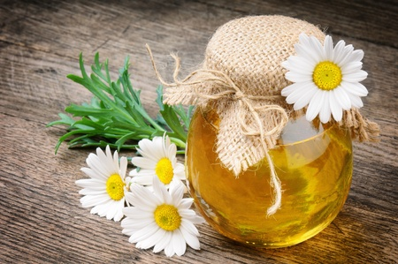 honey liquid: Glass pot of honey with daisies on wooden table