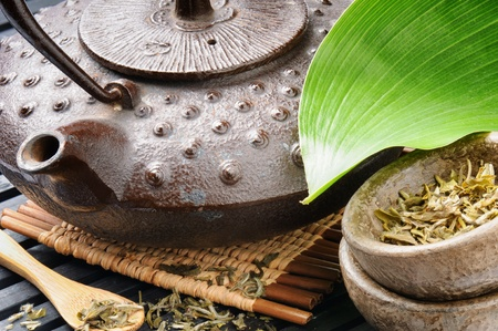 chinese medicine: Asian tea set with green leaf on wooden mat Stock Photo