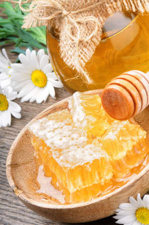 Glass honey pot and comb with daisies photo