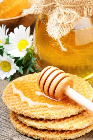 Honey waffles and wooden drizzler on wooden table photo