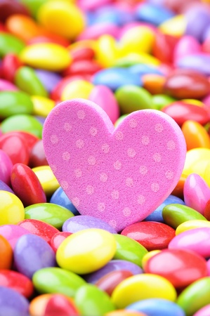 Pink heart and multicolored chocolate smarties photo