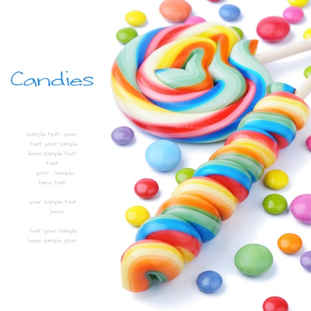 piruleta: Paletas de colores y Smarties aislado en blanco Foto de archivo