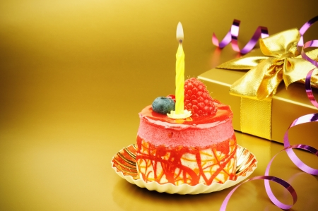 Colorful birthday cake with candle on golden background photo
