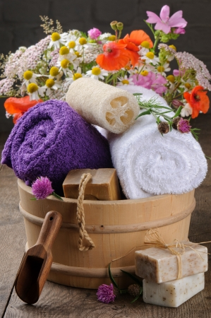 Wooden pail with bath accessories and rural flowers photo