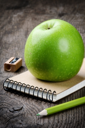 Green apple and school supplies. Ecological concept photo