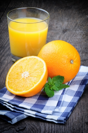 Glass of orange juice and fresh fruits on wooden table photo