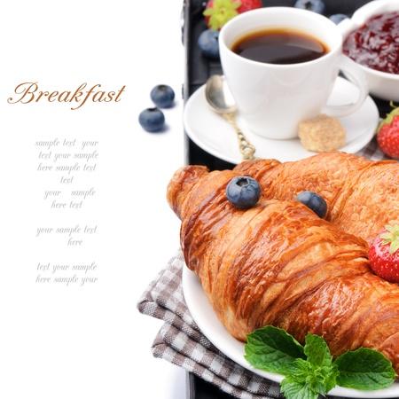 Desayuno con café y croissants frescos sobre blanco Foto de archivo