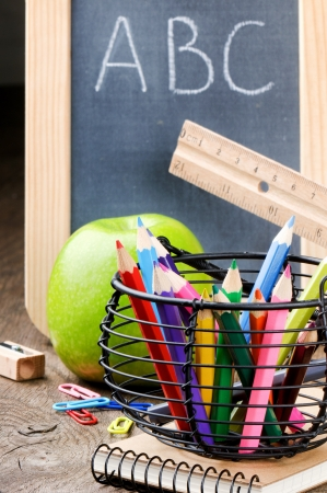 Chalkboard and colorful crayons on wooden desk photo
