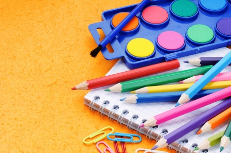 primary colors: Colorful school supplies on orange background
