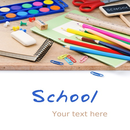 Colorful school supplies on wooden desk background photo