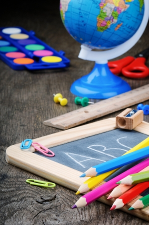 Colorful school supplies on old wooden desk photo