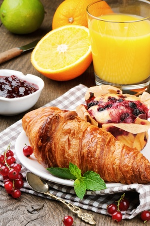 Breakfast with orange juice, fresh croissant and cake on wooden table Stock Photo - 15238877