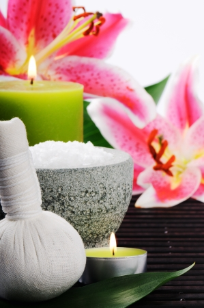 pink lily: Spa setting with sea salt, herbal ball and lily on wooden mat
