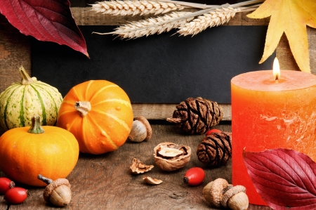 Autumn frame with pumpkins and candle on wooden table photo