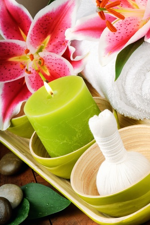 Spa setting with candle, flowers and herbal ball photo