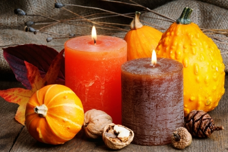 Autumn setting with candles and pumpkins on wooden table photo
