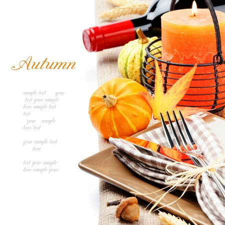 Thanksgiving table setting with pumpkins and candle isolated on white photo