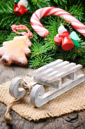 Christmas decoration with mini sleigh on wooden background photo