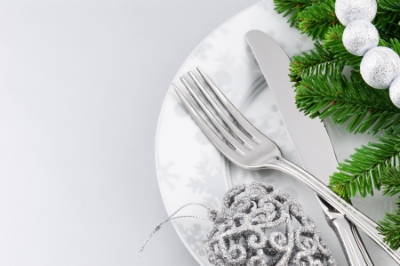 Christmas menu concept with plate and cutlery over silver background