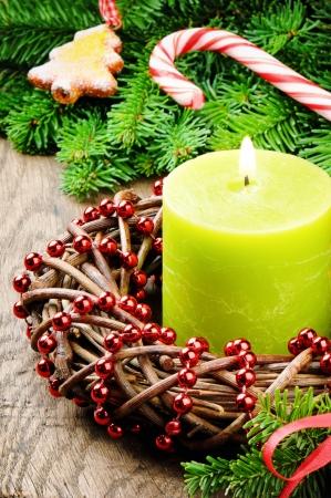 Vánoční adventní věnec s hořící svíčkou a slavnostní dekorace na dřevěném stole
