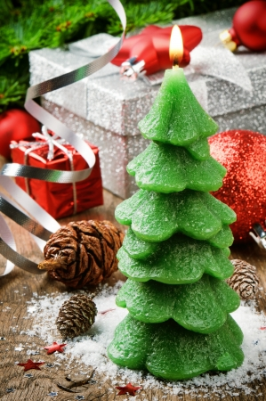 Christmas tree candle on festive background with presents photo