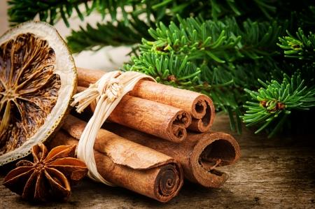 especias: Palitos de canela, naranja y anís seco sobre fondo de Navidad