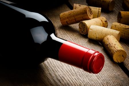 bodegas: Botella de vino tinto y corchos en la mesa de madera