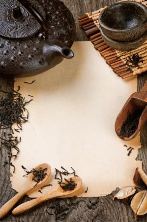 medicina tradicional china: Cap�tulo con el papel de la vendimia y el t� negro seco en la mesa de madera Foto de archivo