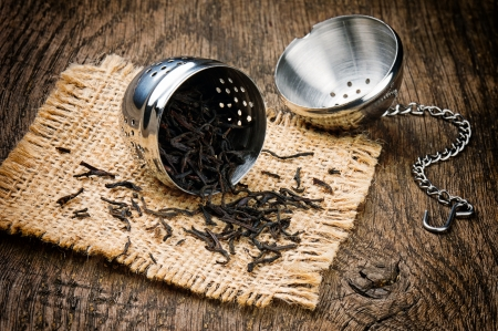 Open metal tea infuser on old wooden table photo