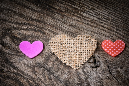 Colorful hearts on rough wooden background photo