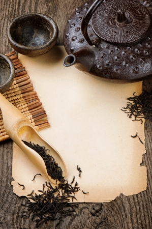Frame with Asian teapot, dried black tea and vintage paper on wooden table photo