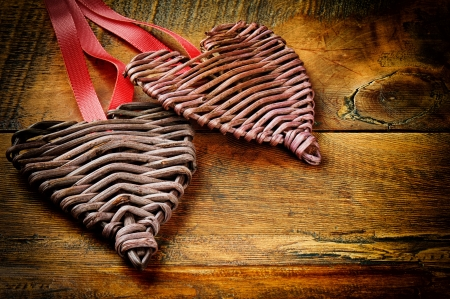 Two wicker hearts on old wooden table photo