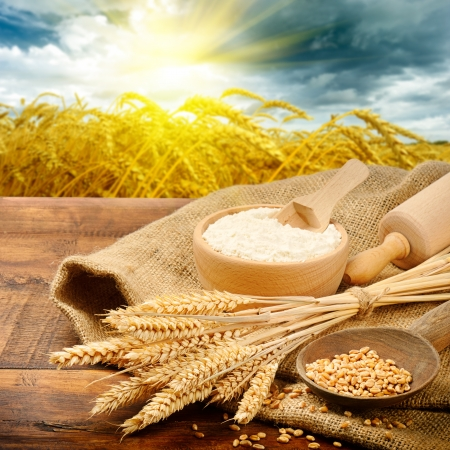 Organic ingredients for bread preparation with golden sunrise on background photo