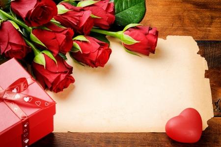 carta de amor: Marco de San Valent�n con rosas rojas y papel de la vendimia en la mesa de madera