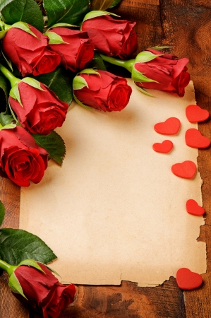 Frame with red roses and vintage paper on wooden table photo