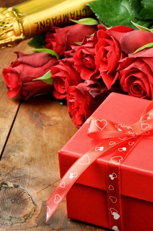 Valentines setting with red roses, champagne and gift box on wooden table photo