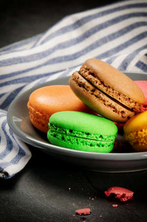 Colorful French macaroons on stone background photo