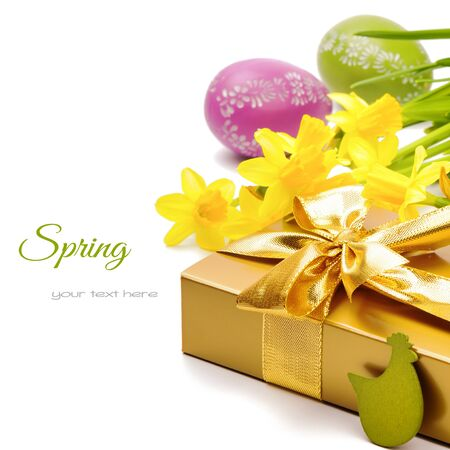 Easter setting with gift box and yellow daffodils isolated over white photo