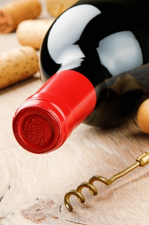 vins: Bottle of red wine and corkscrew on wooden table