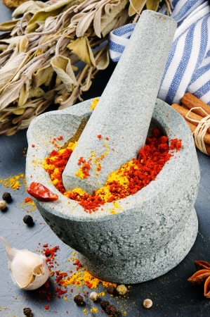 Mortar and pestle with mix of colorful spices on granite background photo